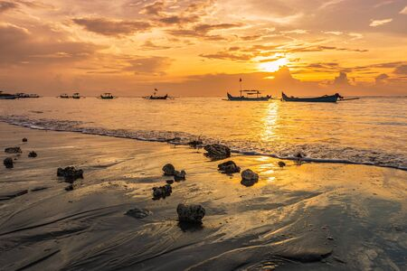 Beautiful sunset on Bali on Kuta beach with colorful clouds and boats in the sea water. Low angle view from the shore on horizon