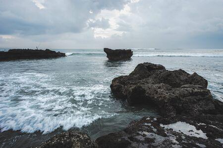 Coastline with rocks and stones and clouds on sky on Pantai Batu Mejan (Echo Beach) Bali Island in Indonesia