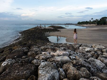Kuta, Bali, Indonesia - October 4, 2016: Locals people and tourists are walking on the shore on the breakwater of stones in the evening in twilight