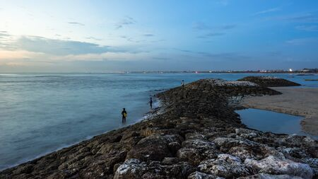 Kuta, Bali, Indonesia - October 4, 2016: Several local fishermen are fishing from the shore in the evening