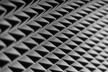 Grey acoustic foam pyramid repeating background for music Studio. Black and white.