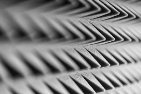 Grey acoustic foam pyramid repeating background for music Studio. Black and white. Close-up view with shallow depth of field Stock Photo