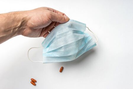 Medical protective mask from virus and infections in a man's hand. Close-up view on a white background with space for text