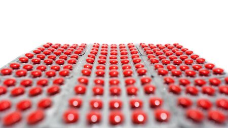 A lot of red round tablets in a packs in a row. Pharmaceuticals and pills on a white background. Space for copy and  text. Blurred foreground. Shallow depth of field with focus on background 版權商用圖片
