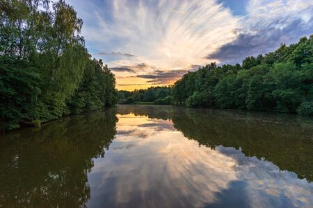 Scenery picturesque sunset with dramatic clouds on sky on calm Desna river in Zarechie in Troitsk