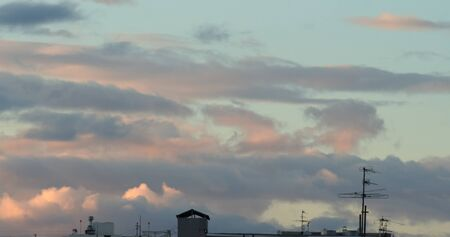 Beautiful sunset clouds over the roof in city background 版權商用圖片