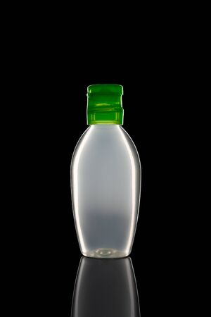 One small bottle of antiseptic liquid sanitizer disinfectant gel for hands with an closed green lid on a black isolated background