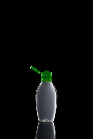 One small bottle of antiseptic liquid sanitizer disinfectant gel for hands with an open lid on a black isolated background