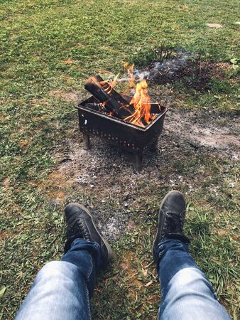 A chargrill with burning wood is in the nature on green grass. A man sits by the fire during the day and relax. First-person view of a man's legs. Self-isolation away from everyone