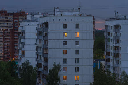Russia, Moscow, Troitsk - June 1, 2020: Cityscape close-up view on  Mikroraion V street residential buildings in the evening twilight with light in apartment windows - district of town TINAO region 新聞圖片