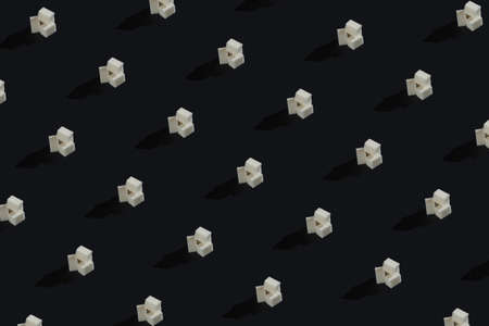 White refined cubes sugar on dark background repeating pattern