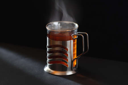 A cup of hot black tea in glass with rising steam in sunlight in cozy dark atmosphere with copy space and black background