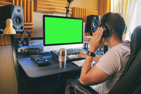 A man produce electronic music in home studio using headphones and look in green screen on monitor 版權商用圖片 - 152274748