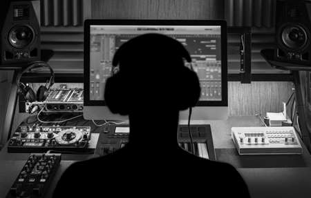 Man produce electronic music in project home studio. Silhouette. Black and white photo
