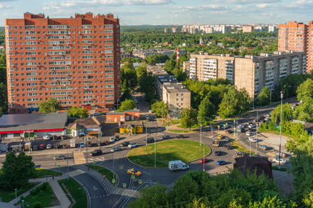 Russia, Moscow, Troitsk - June 1, 2021: Moving transport on circle crossroad in Mikroraion in sunny summer day. Cityscape from high-angle 新聞圖片