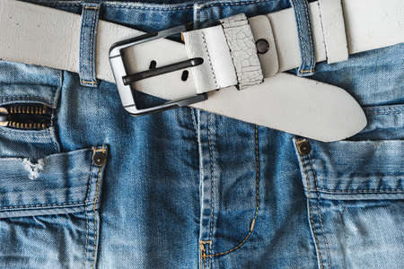 Blue casual jeans with white belt and pockets. Detail flat lay close-up view from above. Textured natural background