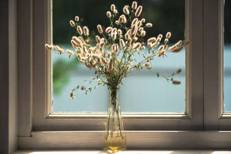Dried field grass decoration in a vase on the windowsill in a rural house. Vintage faded colors