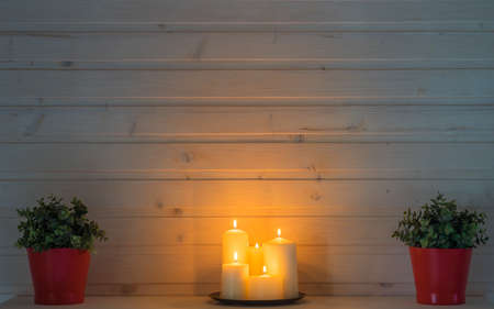 Burning candles and pots with plants in cozy home - background for interior design