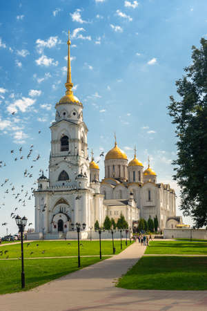 Holy Assumption Cathedral Orthodox church in Vladimir - An outstanding monument of white stone architecture of pre-Mongol Russia. Scenic view in sunny summer day with blue sky and fly birds