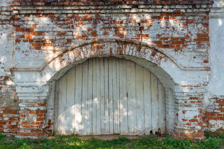 Ancient Russian wooden gate arch in a brick wall of the Kremlin in Vladimir city