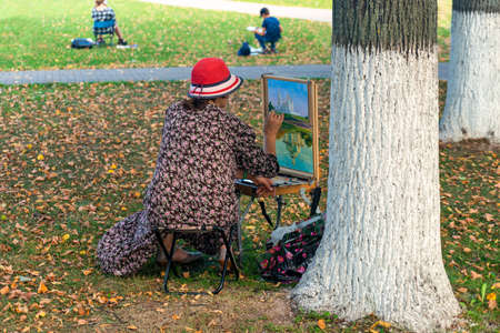 Vladimir, Russia - August 18, 2021: A female painter draws a picture a holy Assumption Cathedral Orthodox church outdoors in the autumn in the park
