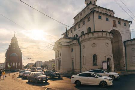 Vladimir, Russia - August 18, 2021: Transport moving on street near Golden Gate architecture landmark in sunny summer evening 新聞圖片