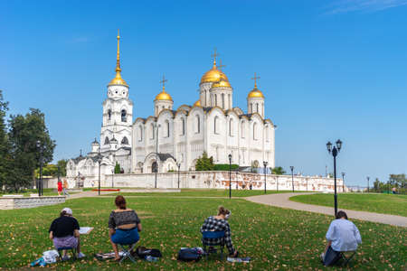 Vladimir, Russia - August 18, 2021: A people artist paints a picture a holy Assumption Cathedral Orthodox church outdoors in the autumn sunny day in the park 新聞圖片