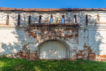 Ancient Russian wooden gate arch entrance in a old brick wall of the historic building or territory of kremlin