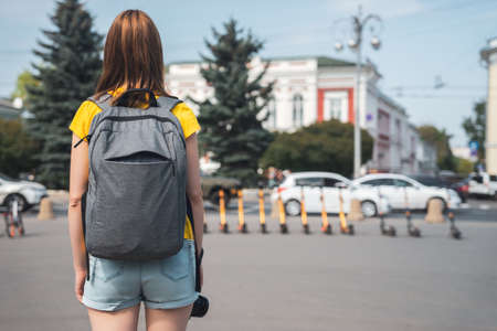 Woman travel in city with backpack, standing and looking on street with transport. Rear view and defocused background