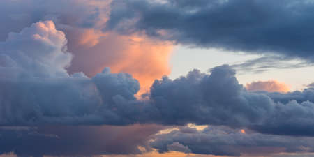 Beautiful colored dramatic cumulus clouds on sky at sunset