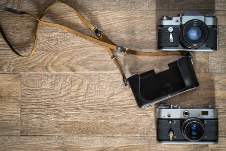 Old retro style film photo camera and leather case on wooden background. Flatlay view from above with space for copy and text