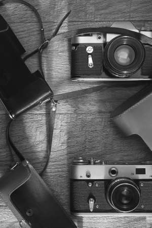 Photographic equipment - old retro film photo cameras and leather cases on wooden background. Black and white image. Flat lay top view