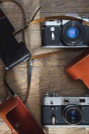 Photographic equipment - old retro film photo cameras and leather cases on wooden background. Flat lay top view 版權商用圖片