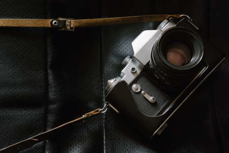 Old retro photo camera with lens on black leather background