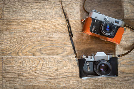 Retro photo cameras on wooden background. Flat lay view from above with space for copy