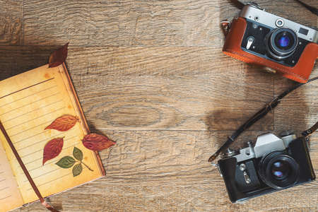 Old retro photo cameras in leather cases on wooden background. Autumn Composition with dry colorful leaves and notepad. Flat lay view from above with copy space