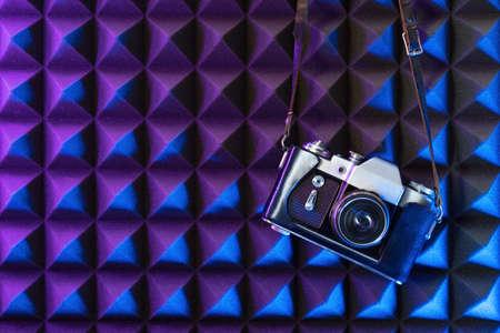 Old vintage photo camera in vivid neon purple and blue light on textured background 版權商用圖片