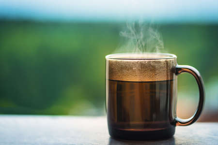 Hot drink or tea in a cup outdoors.  Steam rises up in cold weather. Copy space