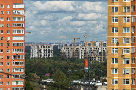 Construction of new residential buildings and residential areas by cranes in Troitsk town. Urban sprawl.