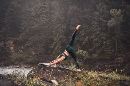 A young blonde woman practices yoga on nature on a stone near a raging river. Green tracksuit. Stock Photo