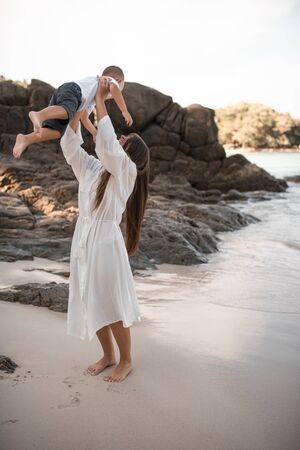 Happy smile european family have rest and run on white sand beach. Father, long black chestnut hair mother, blond baby boy. white cotton clothes. boho dress. t-shorts.Thailand. Aquamarine crystal sea