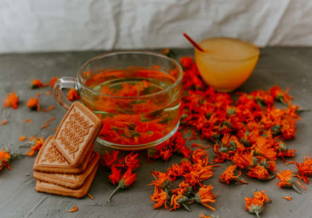 Tea with calendula flowers and biscuits. Transparent glass cup and saucer. Medicinal herbal dried plants marigold, orange calendula. Neutral white and gray background.
