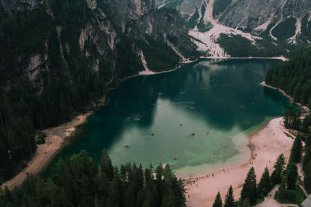 A large clear azure aquamarine green lake with brown wooden boats. High snow-capped stone mountains. Aerial top view from drone.