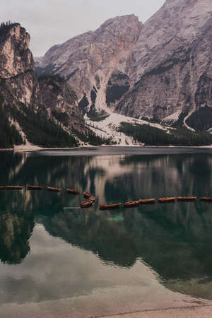 romantic place with brown wooden boats stand on the azure water on the alpine lake Lago di Braies. Dolomites, South Tyrol, Italy, Europe. italian alps.