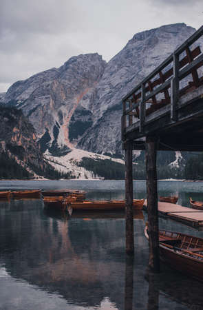Amazing view of Lago di Braies, Pragser wildsee. Trentino Alto Adidge, Dolomites mountains, South Tyrol, Italy, Europe. Boats at the lake. Fanes-Sennes-Braies national park. brown boats