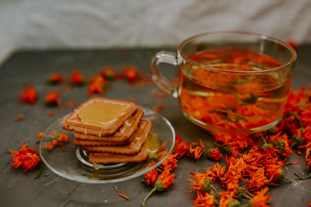 The honey flows in a thin stream onto the baked goods. Orange calendula flower tea in a transparent cup and honey-covered cookies in a saucer. Medicinal herbal dried plants marigold,.gray background.