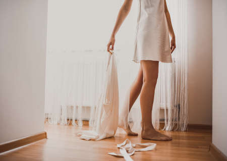 a lady with a veil on her head in white lace underwear goes to the window taking off her silk robe Throwing it on the ground. Orange brown parquet floor. Morning of the bride.
