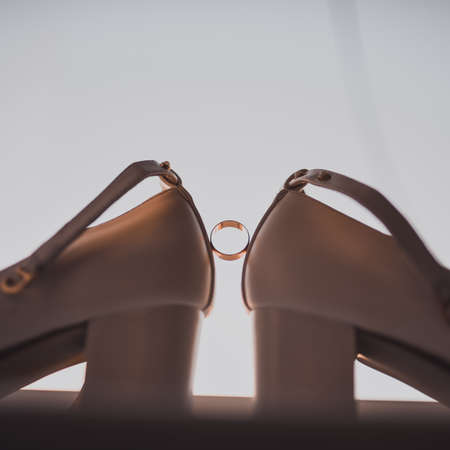 a ring between two womens high heel shoes. Morning of the bride