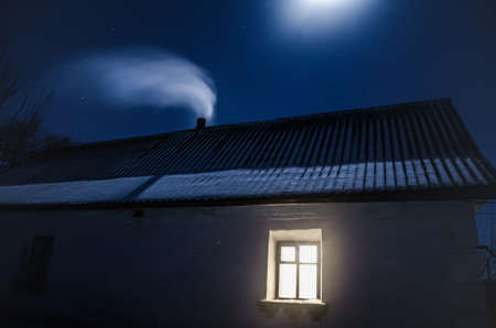 An old little house painted with white lime, a small luminous window,a slate roof. Thick white smoke is coming from chimney moon is shining brightly, dark winter starry nightit up at night