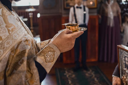 A priest in a golden cassock holds a small mug of sacred red wine on a platter. Stockfoto